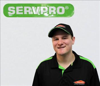 Austin Bucko posing for employee Picture under SERVPRO SIGN