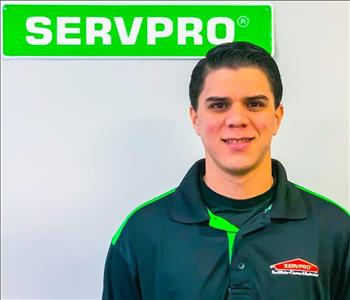 Daniel Gonzalez posing under the green SERVPRO sign for his employee photo