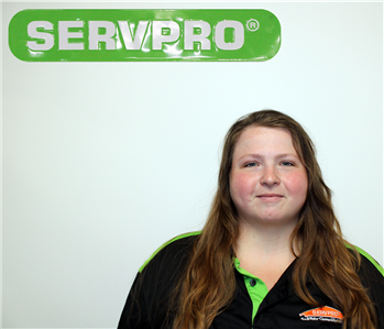 female employee with long hair under SERVPRO sign
