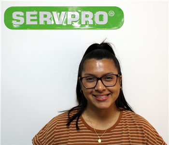Female employee with black hair posing under SERVPRO sign for photo