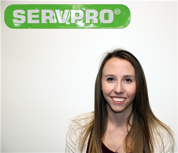 Female employee with long blonde hair standing under green SERVPRO sign