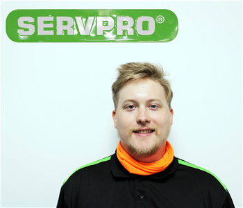 male employee wearing SERVPRO hat and standing under green SERVPRO sign